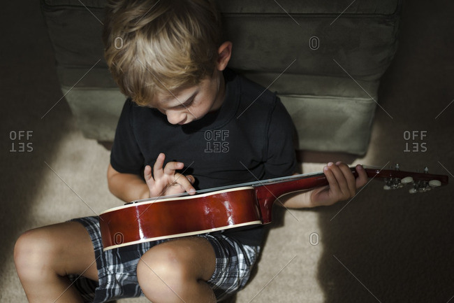 Boy playing with a ukulele on the floor