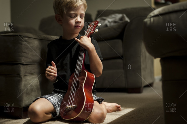 Boy playing with a ukulele on the floor in the living room