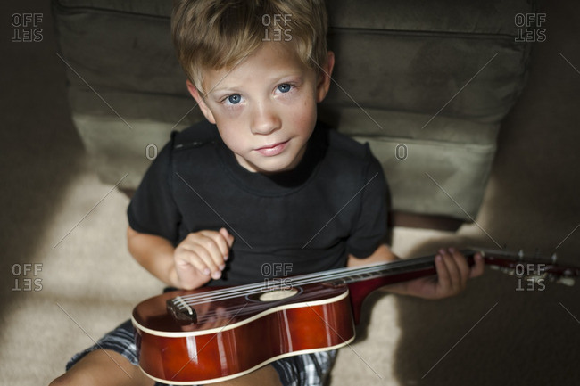 Boy playing with a ukulele in the living room