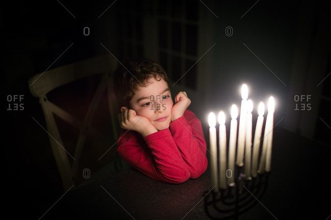 Boy gazing at lit candles on a menorah