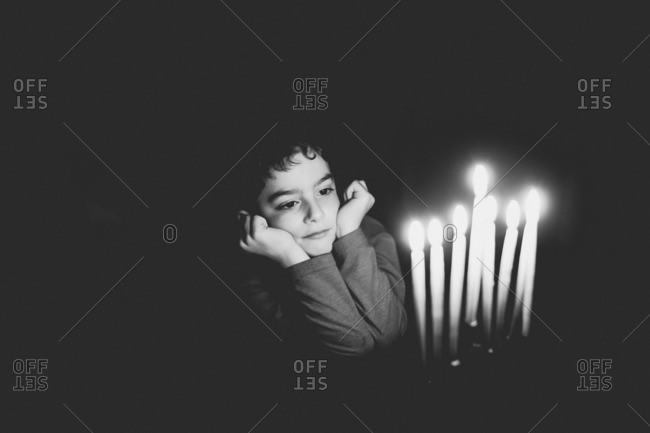 Young boy sitting at table with candles lit in menorah