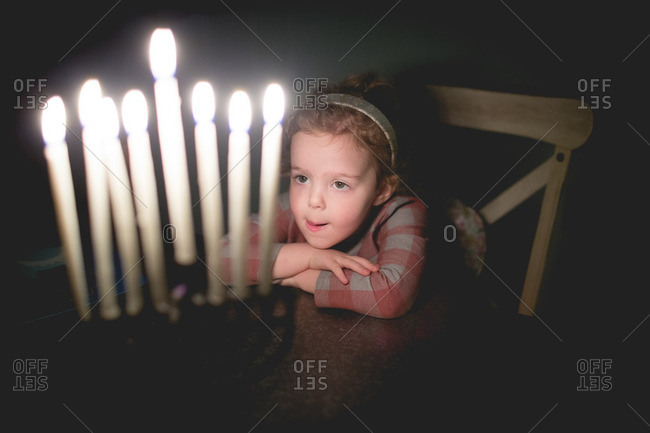 Young girl sitting at a table with candles lit in a menorah