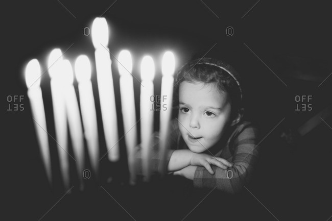 Girl gazing at lit candles on a menorah