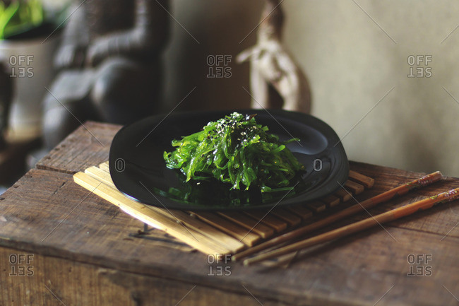 Green seaweed salad on a plate with chopsticks