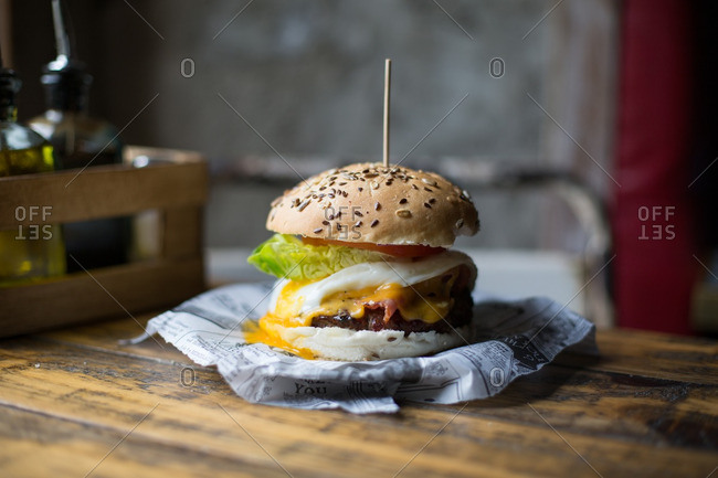 Cheeseburger with fried egg, bacon, lettuce and tomato