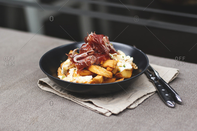 Potato wedges with cheese sauce and thinly sliced cured meat