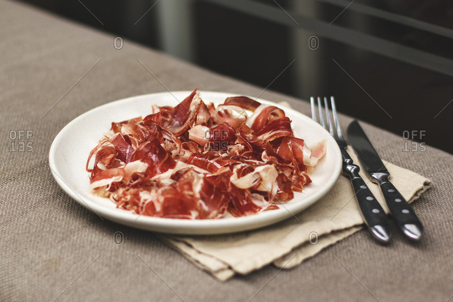 Thin slices of meat served on a platter with a fork and knife