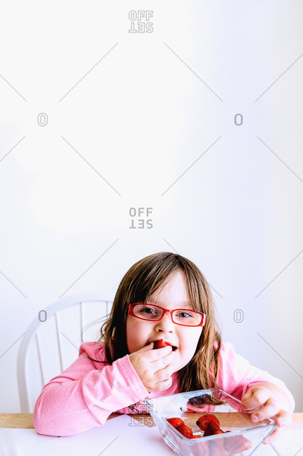 Portrait of young girl with glasses eating strawberries at table