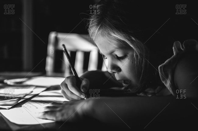 Girl sitting at a table working on her penmanship