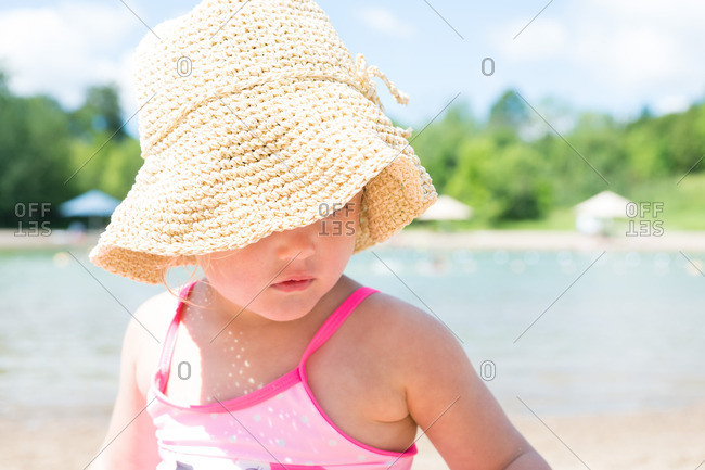 Portrait of a toddler girl wearing a sun hat at the beach