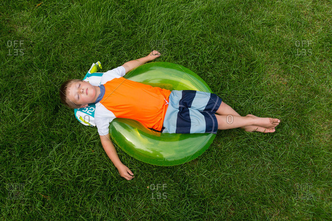 Boy relaxing on an inner tube on the lawn