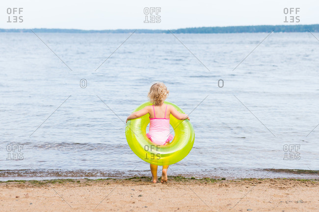 Toddler girl with an inner tube standing at the shore of a lake