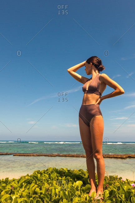 Woman in a bathing suit standing on vegetation next to the beach