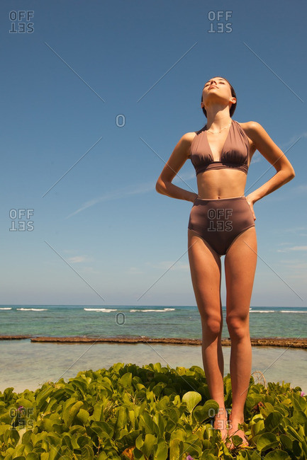 Woman in a two-piece swimsuit standing on a tropical beach