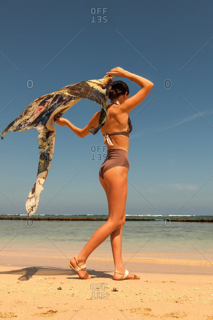 Beautiful woman in a two-piece swimsuit walking on a tropical beach