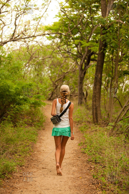 Woman hiking on a trail in a tropical environment