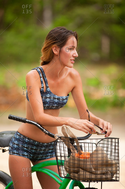 Woman wearing a two-piece swimsuit on a beach cruiser
