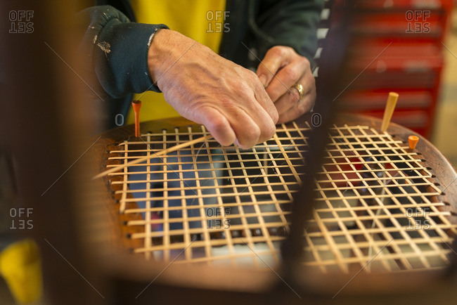Close-up of an artisan caning a chair