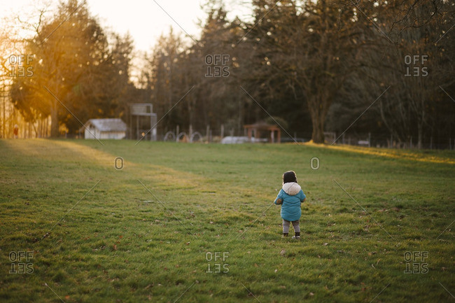 Child in rural field with sunlight