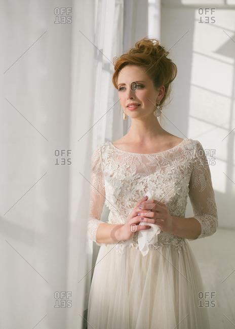 Bride in tulle dress by window