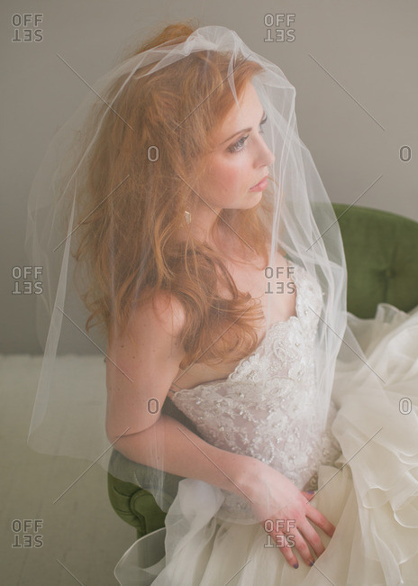 Bride with veil sitting in chair