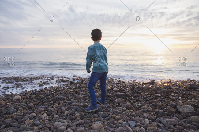 Boy throwing rocks into ocean at dusk