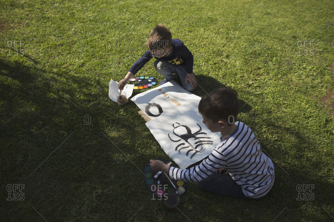 Two young boys painting watercolors outdoors