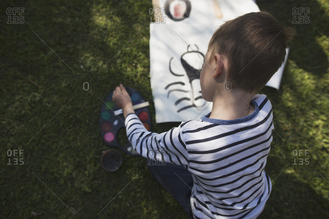 Overhead view of young boy painting with watercolors on lawn