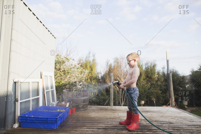 Boy in red rubber boots watering plants in blue bins