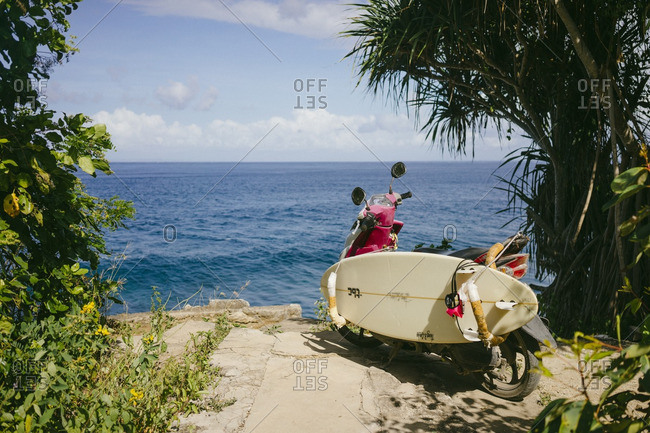 Bali, Indonesia - August 23, 2016: Scooter with a surfboard parked near the edge of a sea cliff