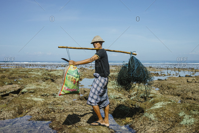 Bali, Indonesia - August 24, 2016: Seaweed harvester standing on rocks at low tide