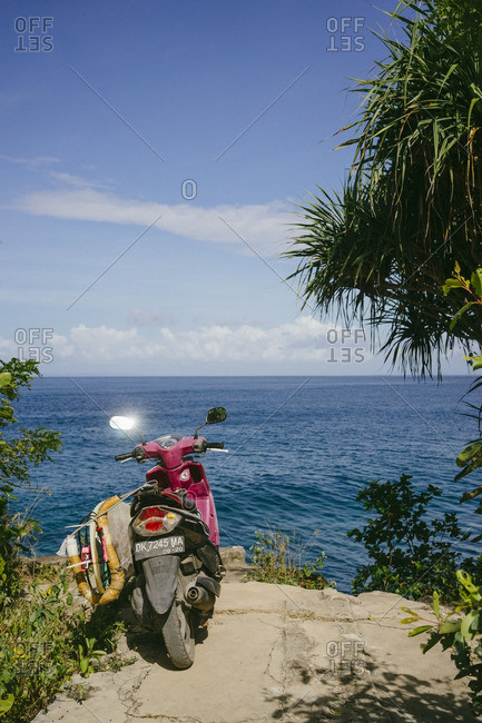 Bali, Indonesia - August 23, 2016: Scooter with surfboard attached on a sea cliff