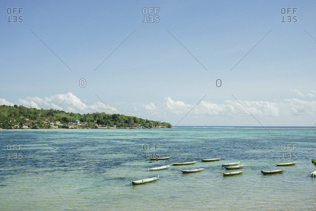 Small boats moored in shallow waters along the coastline of Bali