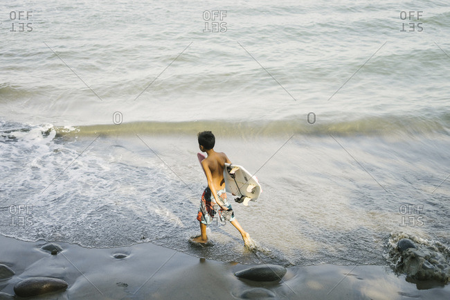 Bali, Indonesia - August 20, 2016: Boy carrying a surfboard on a beach