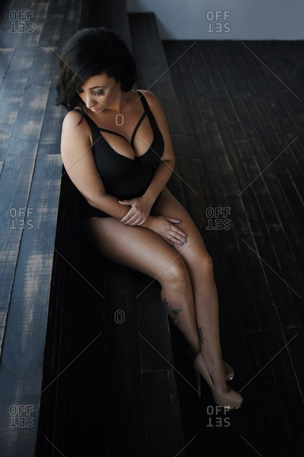 Woman wearing a bathing suit reclining against a set of wood steps