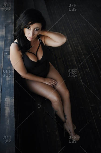 Portrait of a woman wearing a bathing suit reclining against a set of steps