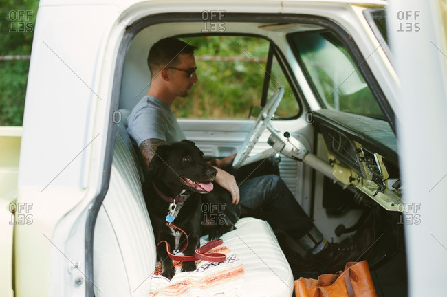 Man sitting in his truck with his dog next to him on the front seat