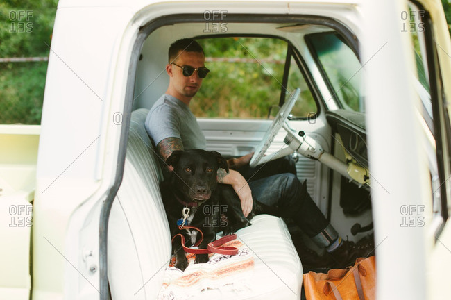 Man sitting in his truck with his dog next to him
