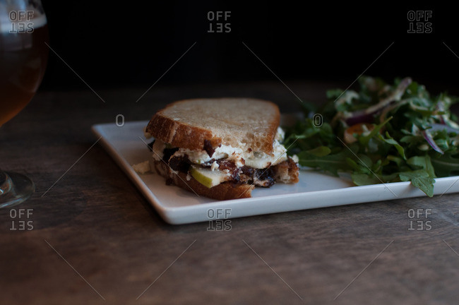Sandwich with a bite taken out of it served on a plate with salad