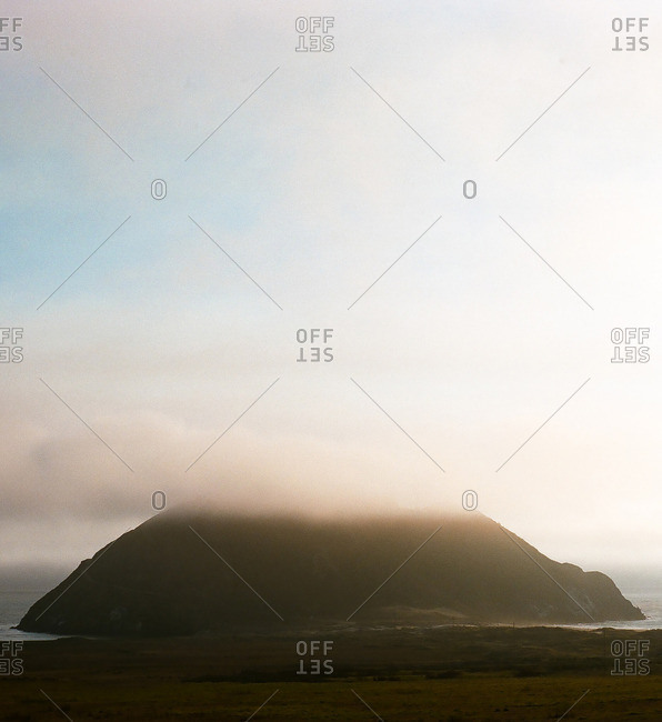 Coastal fog over the top of a large rock in the ocean
