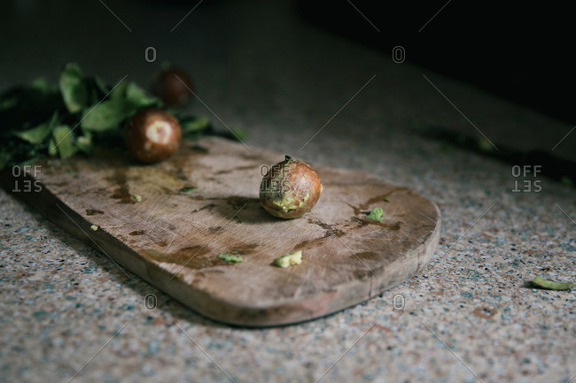 Avocado seeds and fresh greens on a wooden cutting board