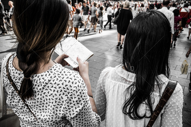 Back view of two young female travelers walking along London street with map