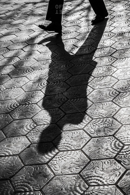 Shadow of person walking on hexagon pattern street