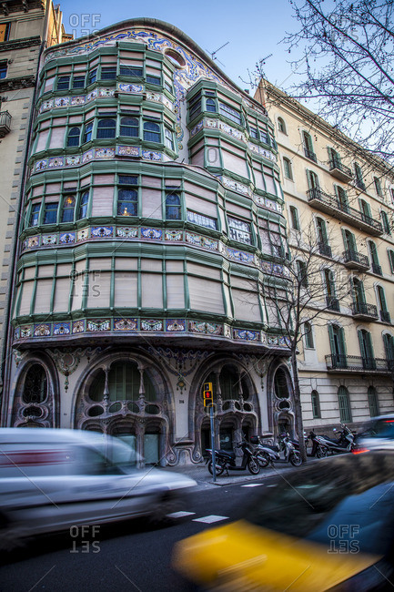 Barcelona, Spain - March 8, 2012: Traffic passing the Casa Comalat by Salvador Valeri Poporull, in Eixample district in Barcelona, Catalonia, Spain