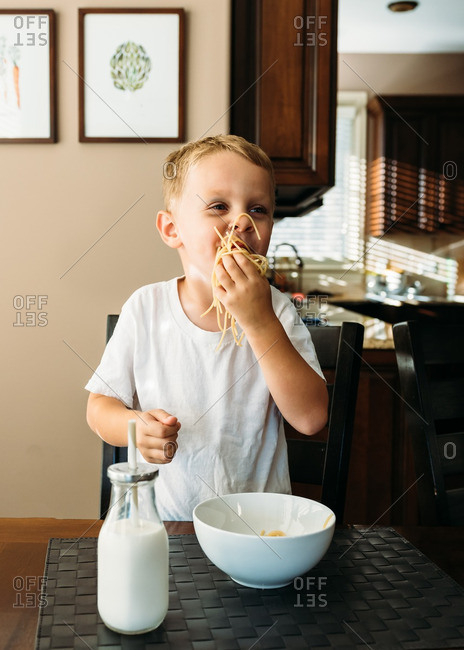Boy eating noodles with hands