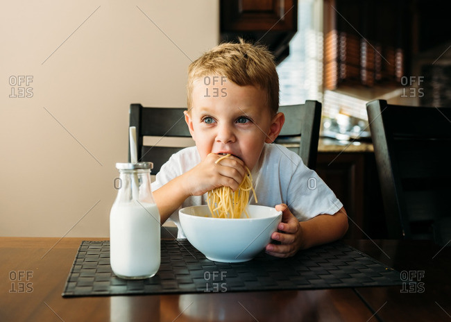 Boy eating noodles by hand