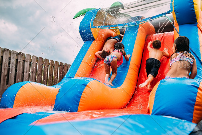 Kids playing on a bouncy waterslide