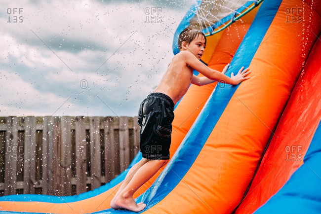 Boy climbing bouncy waterslide