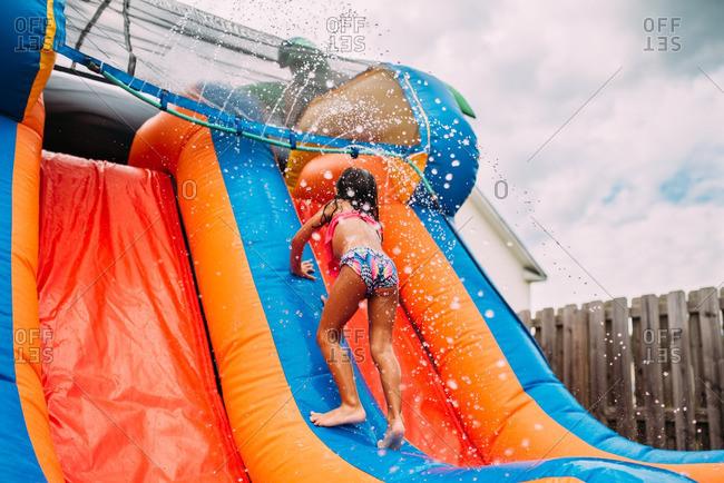 Girl climbing bouncy waterslide