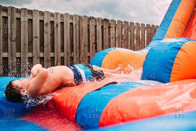 Boy going down backwards on waterslide